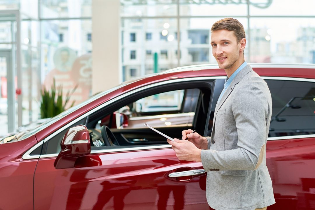 Handsome Sales Assistant Presenting Cars